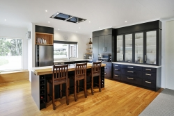 Kitchen island with induction stove and extractor fan inset in ceiling