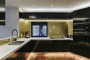 Glass gold splashback runs the length of the kitchen