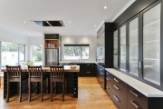 Timber flooring beneath black kitchen cabinetry
