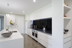 White galley style kitchen with black splashback