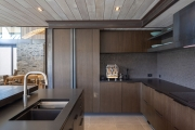 Timber veneer cabinets with raw steel feature
