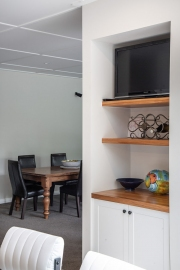 Recessed TV cabinet with cupboards and shelves