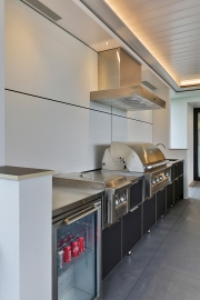 Bar fridge and BBQ in outdoor kitchen cabinets