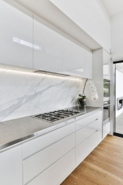 Gloss acrylic cabinets and marble splashback