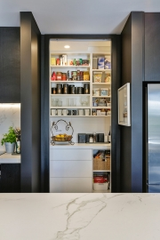 White scullery behind black kitchen