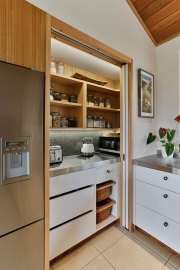 Sliding doors open to reveal storage and workspace