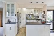 Small kitchen with tui bird splashback