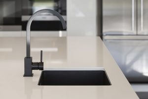 black sink and tap on with kitchen bench