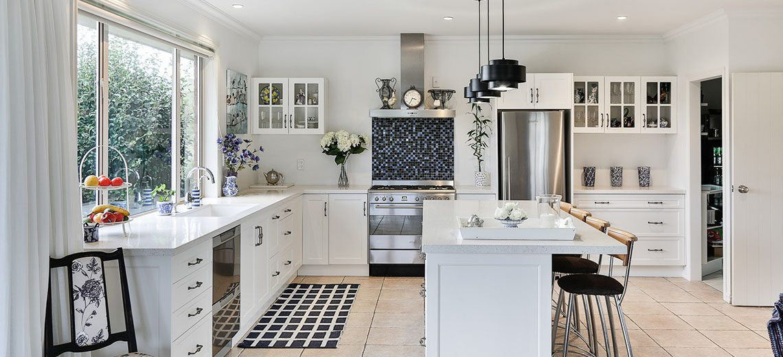 white country kitchen with timber bar stools black pendant lights